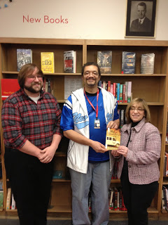 Contemporary novelist Randolph Randy Camp being honored by the Buffalo Erie County Public Library staff for having his three novels go into circulation at all local branches.
